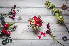 Mazzo delle rose rosse, dei cuori, delle calle, dei garofani e dei nastri sulla tavola Fotografia Stock Libera da Diritti