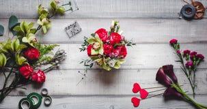 Mazzo delle rose rosse, dei cuori, delle calle, dei garofani e dei nastri sulla tavola Fotografia Stock