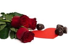 Mazzo delle rose rosse, del cuore di carta rosso e delle caramelle Fotografia Stock Libera da Diritti