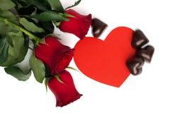 Mazzo delle rose rosse, del cuore di carta rosso e delle caramelle Fotografie Stock