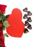Mazzo delle rose rosse, di due cuori di carta rossi e delle caramelle Fotografie Stock