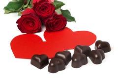 Mazzo delle rose rosse, di due cuori di carta rossi e delle caramelle Immagine Stock
