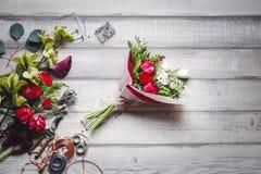 Mazzo delle rose rosse e bianche, dei cuori, delle calle, dei garofani e dei nastri sulla tavola Fotografia Stock