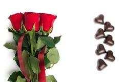 Mazzo delle rose rosse e delle caramelle in una forma di un cuore Fotografia Stock