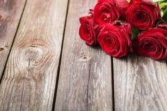 Mazzo delle rose rosse su fondo di legno Backgrou di giorno di biglietti di S. Valentino Fotografia Stock