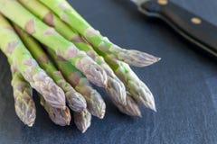 Mazzo di asparago verde fresco su un fondo scuro dell'ardesia, orizzontale immagine stock