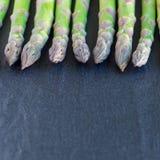 Mazzo di asparago verde fresco sul fondo scuro dell'ardesia, formato quadrato, spazio della copia immagini stock