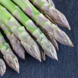 Mazzo di asparago verde fresco sul fondo scuro dell'ardesia, formato quadrato fotografie stock libere da diritti