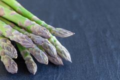 Mazzo di asparago verde fresco sul fondo scuro dell'ardesia, orizzontale, spazio della copia immagini stock