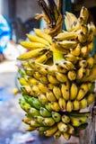 Mazzo di banane gialle allegate al gambo da vendere nel supermercato fotografie stock libere da diritti