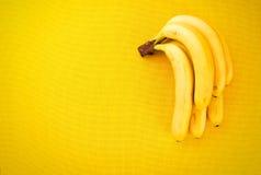 Mazzo di banane mature gialle dai tropici su un tessuto giallo Immagini Stock