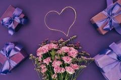 Mazzo di bei fiori rosa, della corda in forma di cuore e dei contenitori di regalo Fotografia Stock Libera da Diritti