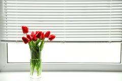 Mazzo di bei tulipani in vaso vicino alla finestra con i ciechi fotografia stock