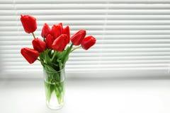 Mazzo di bei tulipani in vaso vicino alla finestra con i ciechi fotografie stock libere da diritti