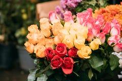 Mazzo di belle rose variopinte con le gocce di acqua nel mercato Fotografia Stock