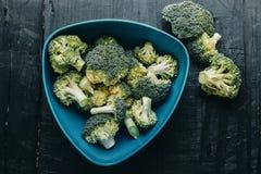 Mazzo di broccoli verdi freschi sopra fondo di legno nero guar immagine stock libera da diritti