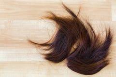 Mazzo di capelli bruno-rossastro tagliati sistemati sul pavimento di legno con fotografia stock