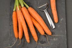 Mazzo di carote e di metallo Peeler fotografia stock libera da diritti
