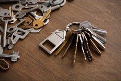 Mazzo di chiavi con il trinklet della casa sulla tavola di legno Immagine Stock