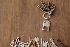 Mazzo di chiavi con il trinklet della casa sulla tavola di legno Fotografia Stock