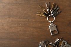 Mazzo di chiavi con il trinklet della casa sulla tavola di legno Immagine Stock Libera da Diritti