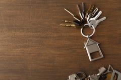 Mazzo di chiavi con il trinklet della casa sulla tavola di legno Fotografia Stock Libera da Diritti