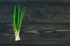 Mazzo di cipolle di inverno fresche delle cipolle verdi in pacco sulla tavola del tagliere Fondo di legno scuro o neutrale Fotografie Stock Libere da Diritti