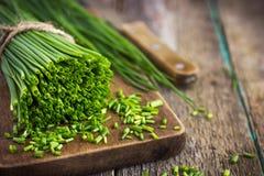 Mazzo di erba cipollina fresca su un tagliere di legno Fotografia Stock Libera da Diritti