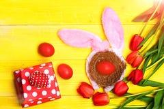 Mazzo di fiori vicino alle uova in nido con le orecchie del coniglietto Fotografia Stock Libera da Diritti