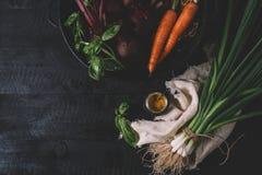 Mazzo di giovani cipolle verdi, barbabietole, carote e basilico su un fondo nero di vecchia annata dei bordi di legno, verdura fr immagini stock libere da diritti