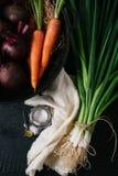 Mazzo di giovani cipolle verdi, barbabietole, carote e basilico su un fondo nero di vecchia annata dei bordi di legno, verdura fr fotografia stock libera da diritti