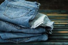 Mazzo di jeans su fondo di legno, vestiti alla moda Fotografia Stock Libera da Diritti