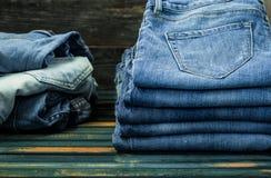 Mazzo di jeans su fondo di legno, vestiti alla moda Immagini Stock Libere da Diritti