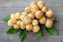 Mazzo di lanzones o frutta e foglie dolci di Longong sulla tavola Fotografia Stock