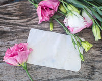 Mazzo di Lisianthus su una tavola di legno con la nota in bianco Immagini Stock