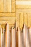 Mazzo di matita con l'ente di legno sul fondo del parquet Immagine Stock