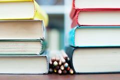 Mazzo di matite colorate fra due mucchi dei libri immagine stock