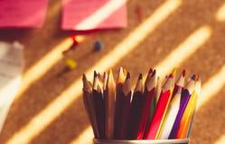 Mazzo di matite variopinte in un supporto davanti al bordo del sughero fotografie stock