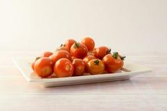 Mazzo di mini pomodori rossi su un piatto Immagini Stock Libere da Diritti