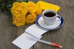 Mazzo di natura morta delle rose gialle, del caffè e del taccuino Immagine Stock