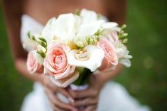 Mazzo di nozze con gli anelli su nelle mani della sposa fotografie stock