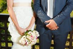 Mazzo di nozze con i fiori rosa in mani dello sposo e del brid Immagine Stock
