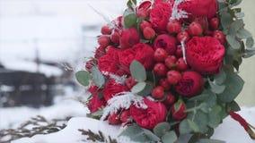 Mazzo di nozze con le fedi nuziali con i fiori rossi sui precedenti di neve stock footage