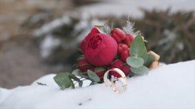 Mazzo di nozze con le fedi nuziali con i fiori rossi sui precedenti di neve video d archivio