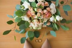 Mazzo di nozze con le fedi nuziali di menzogne vicine a fuoco delle rose beige e rosa, scarpe di beige dei bride's Fotografie Stock Libere da Diritti