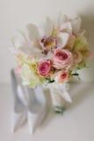 Mazzo di nozze con le orchidee e le rose e la scarpa della sposa di nozze Fotografia Stock
