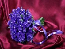 Mazzo di nozze dalle viole su un rosso Fotografie Stock Libere da Diritti