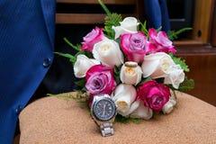 Mazzo di nozze delle rose bianche e rosa-rosso che si trovano su una sedia contro una giacca blu fotografia stock