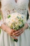 Mazzo di nozze delle rose bianche nella sposa delle mani Immagine Stock