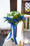 Mazzo di nozze nei colori bianchi e verdi e fedi nuziali in decorazione blu su una superficie bianca fotografie stock libere da diritti
